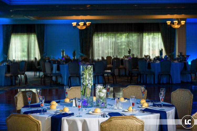 wedding centerpieces and table settings under blue uplighting at Pinecrest Country Club, a wedding venue in Lansdale PA
