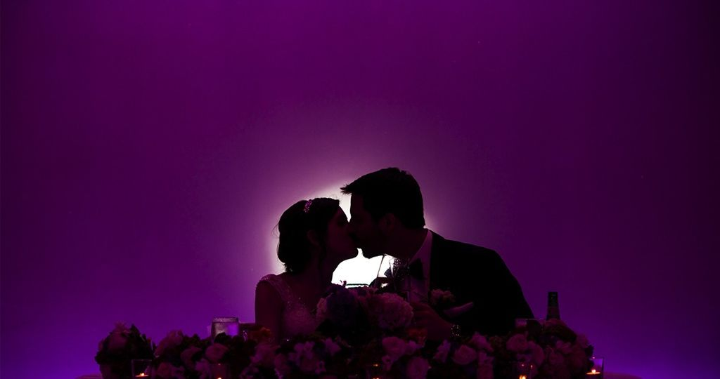 kissing wedding couple seated at the sweetheart table with purple uplighting at a wedding venue in in Lansdale PA