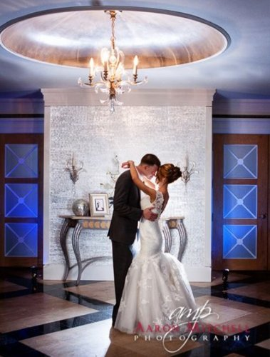 bride and groom under an elegant chandelier at Pinecrest Country Club, a wedding venue near Philadelphia
