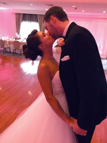 bride and groom in a banquet hall with pink uplighting at Pinecrest Country Club a party space in Montgomery County PA