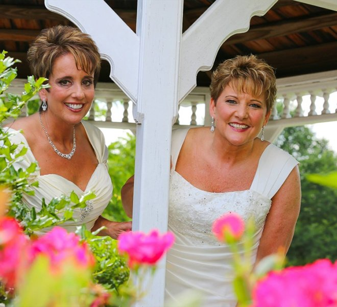 Two brides taking a photo in the gazebo at PineCrest Country Club in Montgomery County, PA