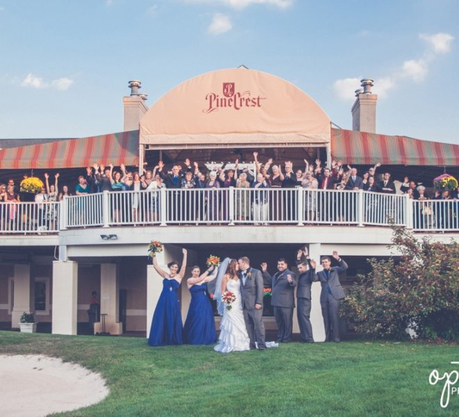 Bridal party on the golf course and wedding guests on PineCrest's deck celebrate with a large group photograph during wedding reception.