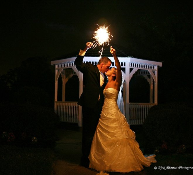 Wedding couple pose with sparklers in front of PineCrest's gazebo at night.