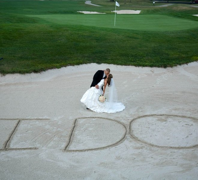 "Wedding couple poses in front of ""I Do"" written in the sand on PineCrest's golf course in Lansdale, PA"