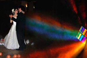 bride and groom dancing in multi-colored outdoor lighting
