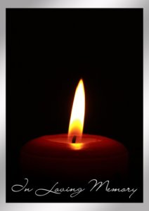 Single lit candle with text that reads In Loving Memory