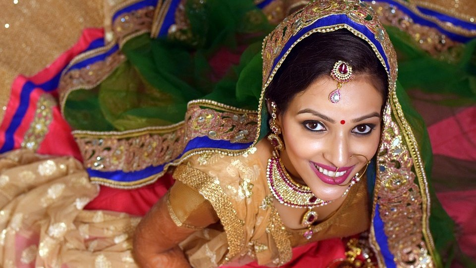 Indian bride dressed in gold, blue and red hues