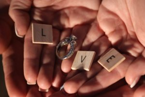Two hands holding an engagement ring and scrabble letters to spell the word Love.