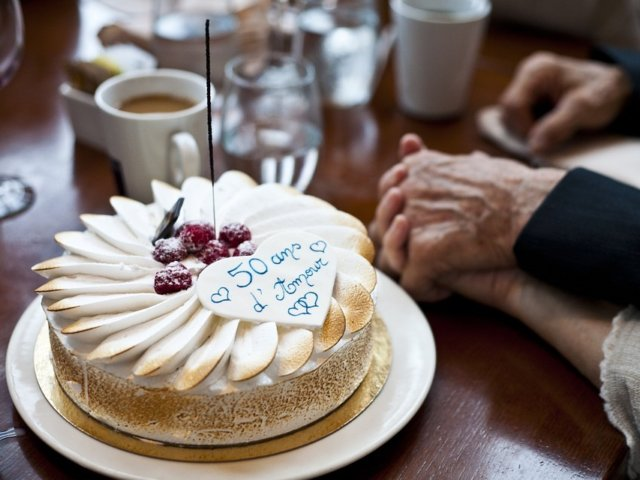 Holding hands next to a white cake that says 50 Years of Love