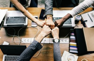 five hands join together to high-five over top of a desk with laptops and other corporate materials