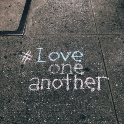 sidewalk chalk that reads hashtag love one another