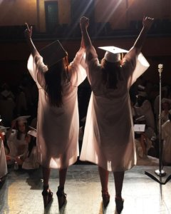 two graduates cheering on stage facing the audience