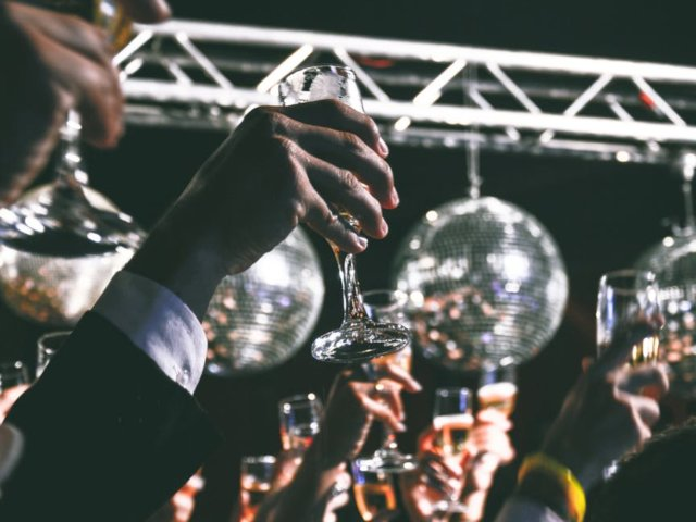Several champagne glasses raised for a toast at a wedding.