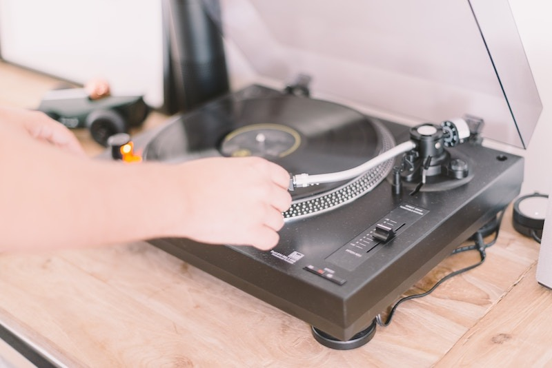 hand moving needle on record turntable