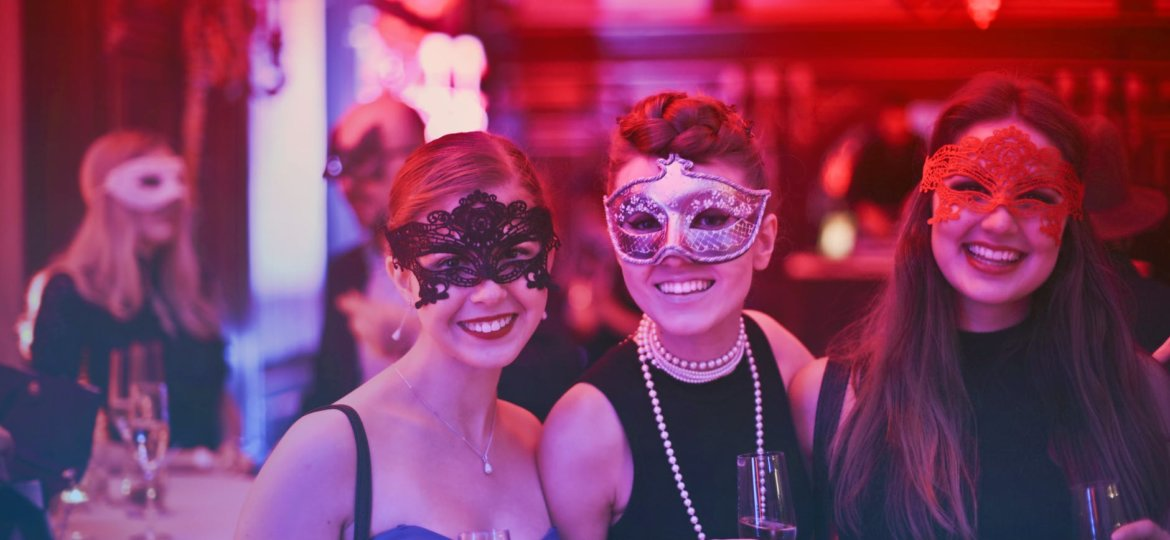 Three young women at a masquerade ball