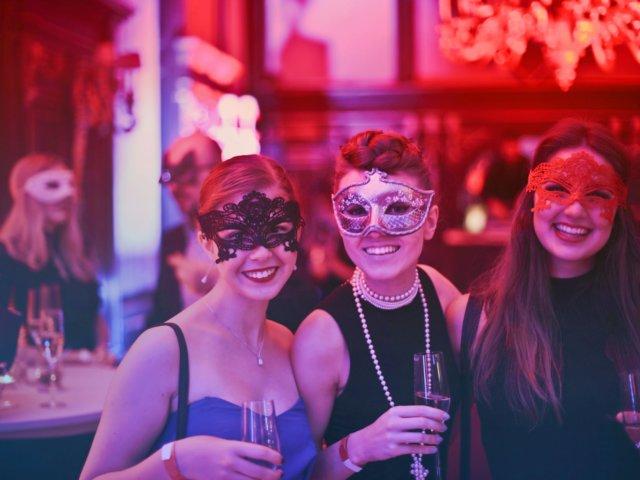 Three young women at a masquerade ball