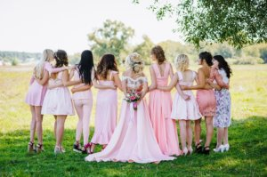 Wedding party dressed in unmatched pink dresses and formal wear.