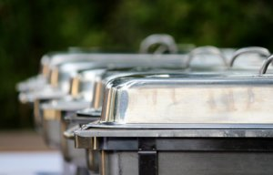 several chafing dishes lined up for a wedding buffet