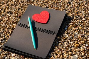 Black paper notebook with red heart and pen.