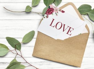 envelop containing a wedding invitation that says Love