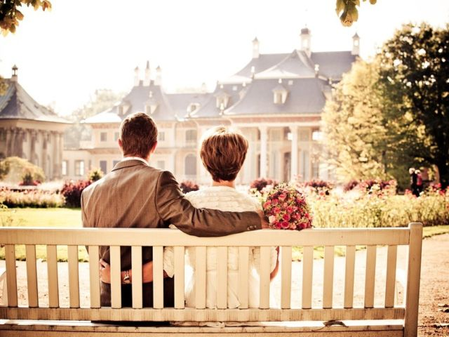 Wedding couple sitting on a bench looking at their reception hall building.