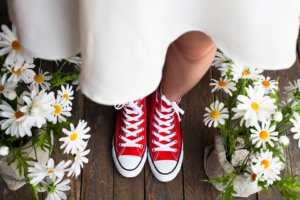 Bride wearing red sneakers under a white dress.