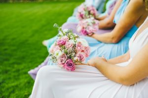 bridesmaids sitting down with flowers in their laps