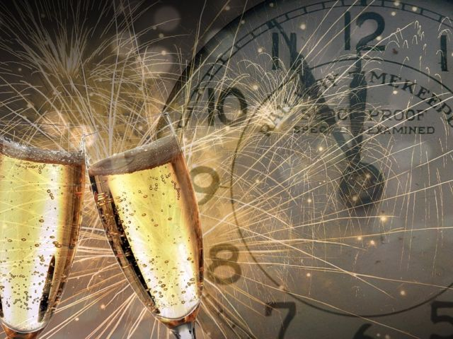 two champagne glasses, fireworks, and a clock