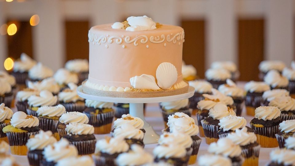 wedding cake and cupcakes on display at a wedding reception