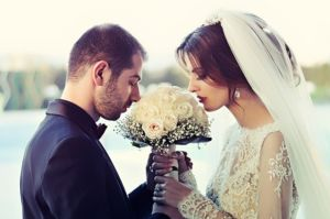 Wedding couple smelling flowers