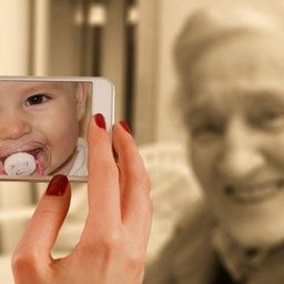Picture of baby on cell phone and old woman