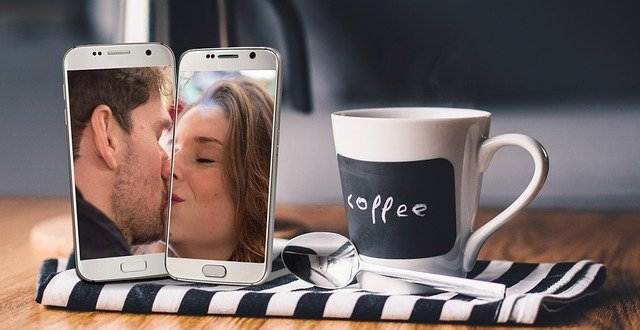 two cell phones each with a person in the camera view kissing