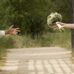 wedding couple reaching out to one another's hands