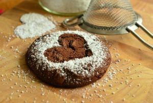single cookie pastry with a heart imprint and powdered sugar