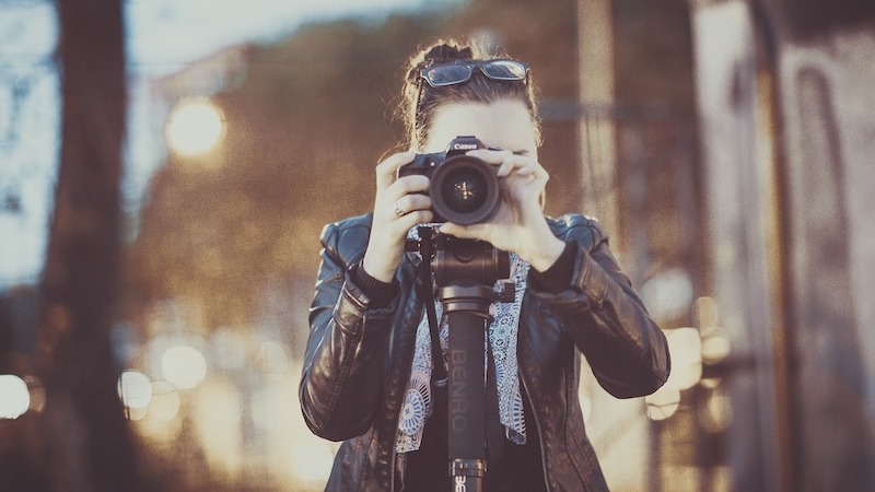 woman holding camera wearing jacket
