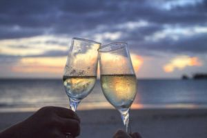 two raised glasses at the beach