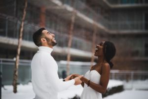 Couple on their wedding day smiling at the falling snow
