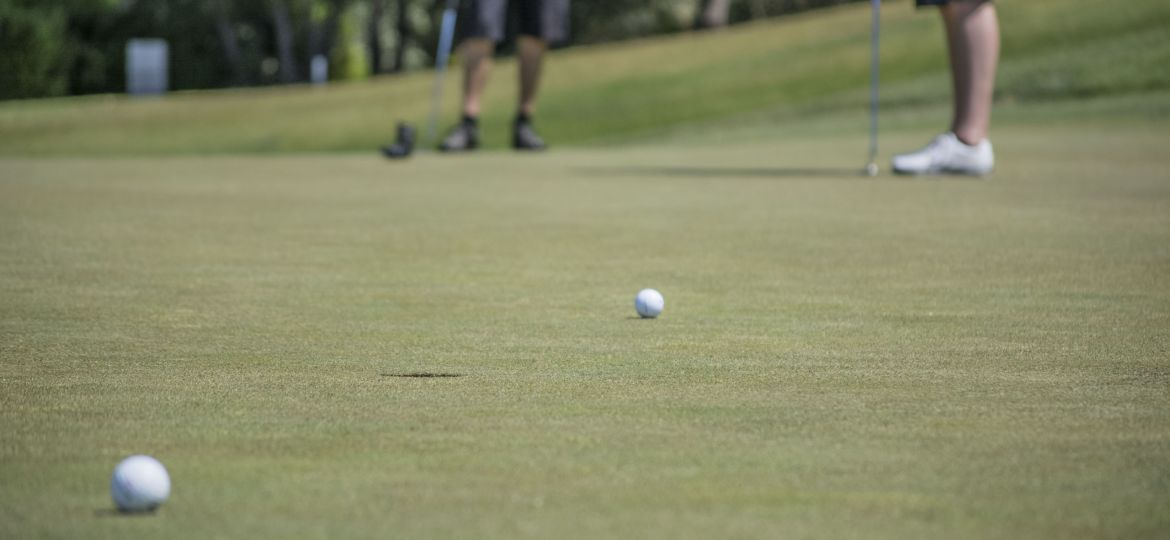 Two men take putts on a golf course green