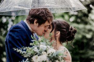 Newly weds share a kiss under an umbrella on a rainy wedding day