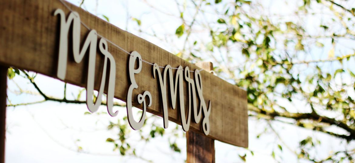 Mr. and Mrs. sign hung outdoors at a wedding celebration