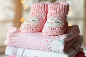 Knitted pink baby booties on top of stack of baby clothes
