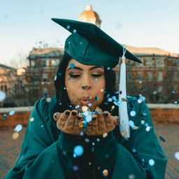 Graduate in cap and gown blowing confetti