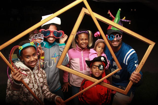 Family posing with photo frames and props at a party photo booth