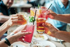 Friends toast colorful drinks together at a summer cocktail party