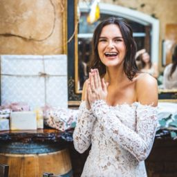 Woman smiling in white dress in front of gifts at a bridal shower