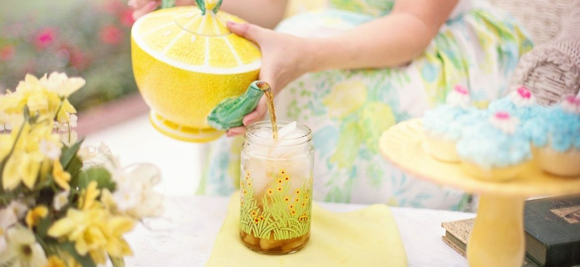 Woman in brightly colored dress pours tea out of a yellow teapot