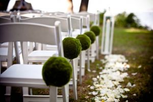 White chairs with green decor line the aisle of an outdoor summer wedding
