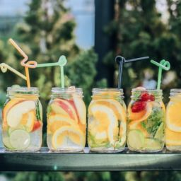 Summer beverages in glass ball jars with colorful fruit and straws