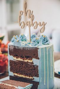 Chocolate cake with blue frosting and an oh baby decoration on top