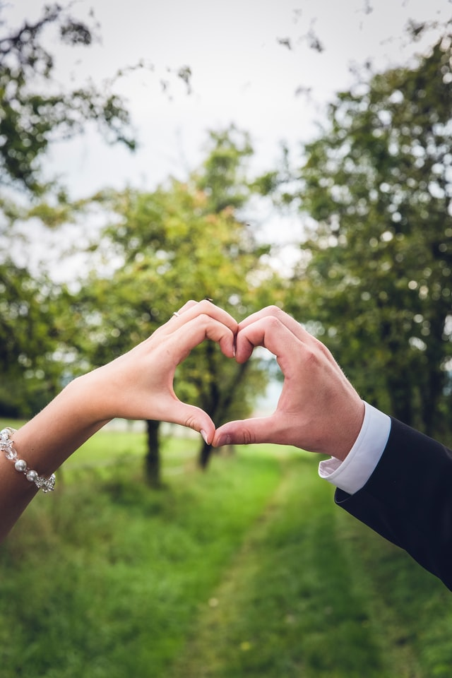 Bride and groom each have one hand forming a heart against a grassy field